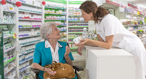 Pharmacist helping an older lady in a wheelchair
